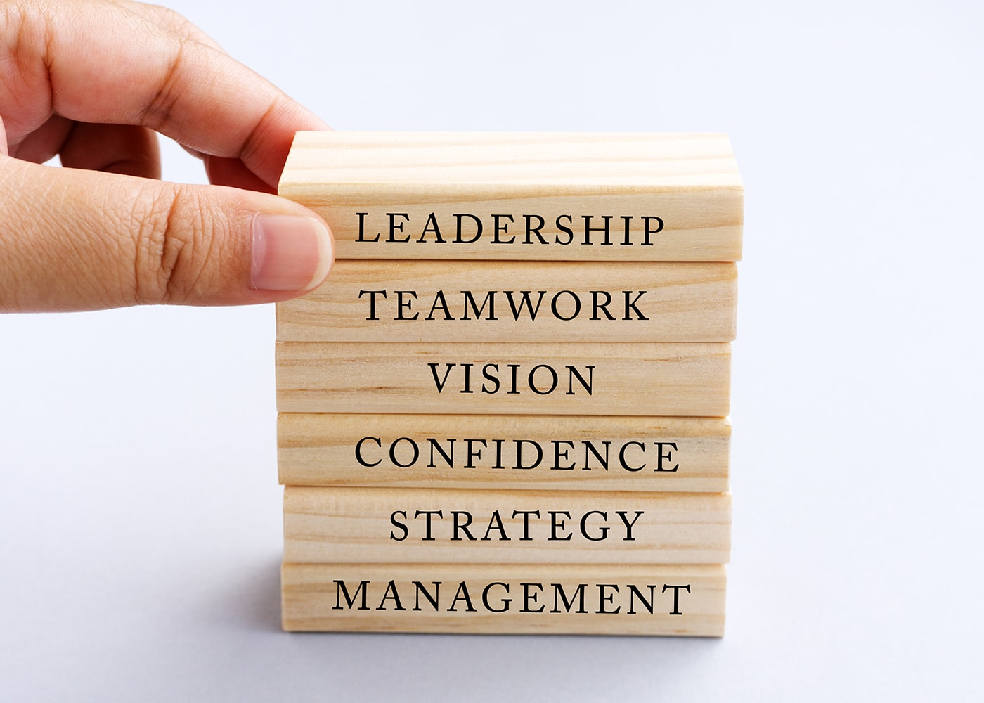 naem-2018-blog-hand-picking-wood-block-word-leadership-700x500