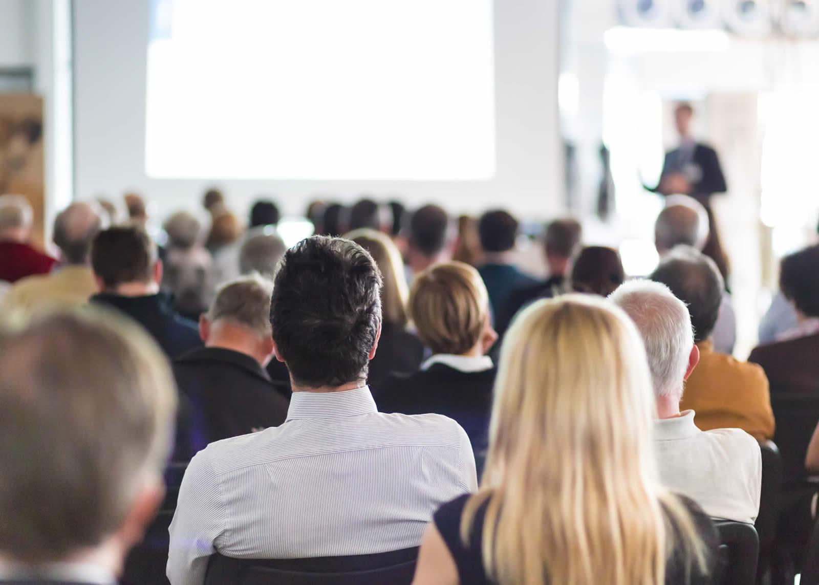naem-2018-speaker-giving-talk-business-meeting-audience-700x500
